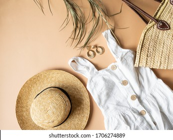 Women's summer straw hat, wicker bag, white sundress, sunglasses  and jewelry on a beige background. Copy space. Top view