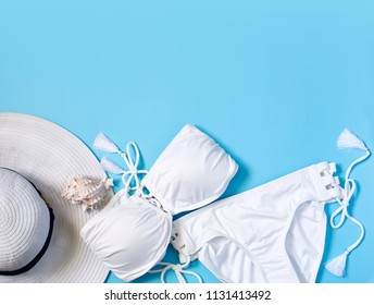 Women's swimsuit, white hat on blue background. Flat lay composition of summer fashion, copy space, top view
