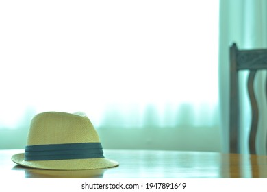 Women's trilby hat.   put on a reflect brightly walnut oval dining table. window is bright.   This expensive antique furniture is made in England.   clear background with soft focus image.