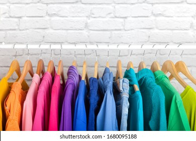 Women's wardrobe sweatshirts shirts and blouses hang on wooden shoulders in the order of all the colors of the rainbow against white brick wall. Concept update in the wardrobe. Advertising space