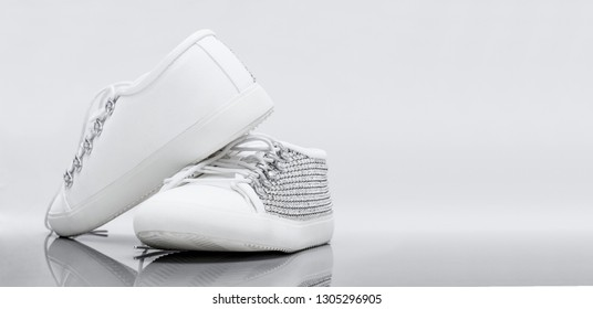 Women's white studded stylish shoes with a white background with copy space for text.