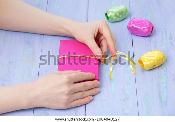 Women'shands wrapped in a pink gift box with a yellow ribbon on a violet wooden background. Cose-up