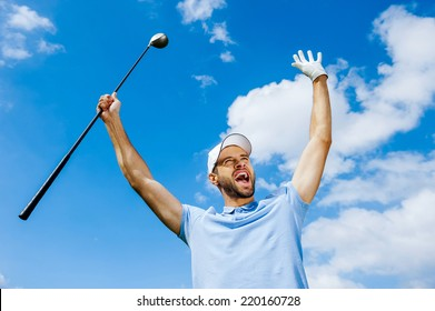 I won! Low angle view of young happy golfer holding driver and raising his arms with blue sky as background