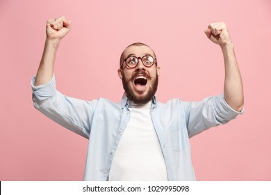 I won. Winning success happy man celebrating being a winner. Dynamic image of caucasian male model on pink studio background. Victory, delight concept. Human facial emotions concept. Trendy colors