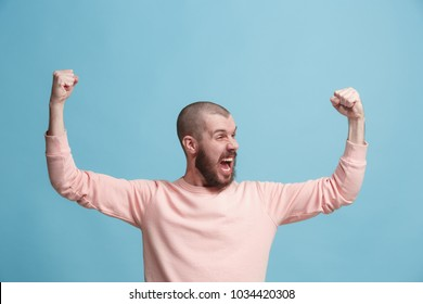I won. Winning success happy man celebrating being a winner. Dynamic image of caucasian male model on blue studio background. Victory, delight concept. Human facial emotions concept. Trendy colors
