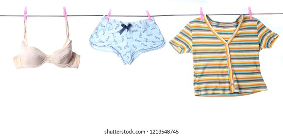 Wonan's bra, panties, t-shirt hanging on a clothesline with buckles isolated on white background. Washed things, washed underwear