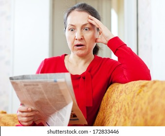 wonder grief mature woman with newspaper