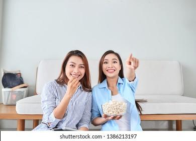 Wondered amazed impressed girl gesturing forefinger eating popcorn watching funny comic program with her friend sitting in living room indoor enjoying interesting film