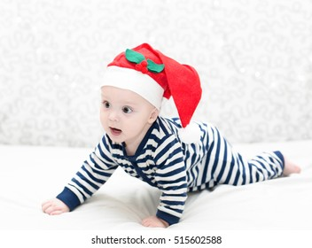 wondered baby boy wearing a crocheted Santa hat on light background, selective focus