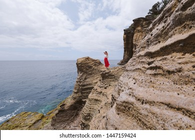 Wonderer woman wearing red dress and hat standing on amazing view cliff looking to ocean