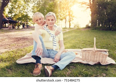 Wonderful activity. Joyful nice elderly couple sitting n the blanket and smiling while enjoying their picnic in the park