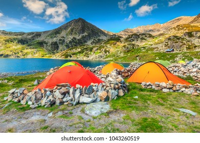Wonderful alpine camping place with colorful tents near Bucura glacier lake. Stunning mountain campground in Retezat Natural Park, Carpathians, Transylvania, Romania, Europe