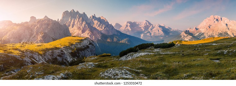 Wonderful Alpine highlands during sunrise. Morning panoramic view of Dololites mountains, Italian Dolomites Alps under sunlight. Awesome landscape with colorful sky over the Cadini di Misurina range.