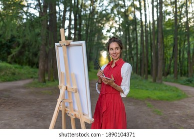 Wonderful artist, Alley trees background. Beautiful woman in red dress in summer in park and forest, draws a picture, creating creativity and landscape. Girl creativity and art concept