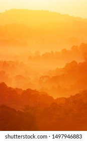 Wonderful autumn mountain in the morning mist, glowing sunrise shines onto autumn forest and mountain range in the background. Soft focus.