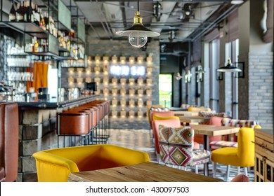 Wonderful bar in a mexican restaurant in a loft style. On the left there is a black bar rack with brown chairs, shelves with dishes and equipment. On the right there are wooden tables with multi
