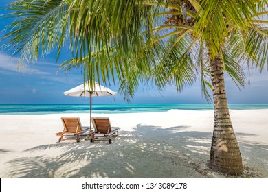 Wonderful beach scenery, two lounge chairs on white sand under palm leaf near blue sea. Perfect island landscape, luxury sumer vacation and holiday concept. Chaise lounge concept on summer beach.