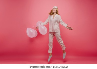 Wonderful birthday girl in cute socks jumping in morning. Full-length indoor photo of excited female model in pyjamas fooling around before party.
