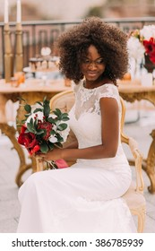 Wonderful black bride happily smiling with eyes closed and holding a bouquet of red flowers. Wedding day