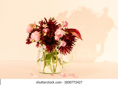 A wonderful Bouquet of autumn flowers as Dahlia Chat Noir and Rose Fairy in a green glass pitcher with a white/pink background