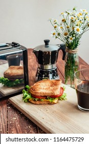 A wonderful breakfast, toast with coffee. Toster, flowers and breakfast on a wooden table