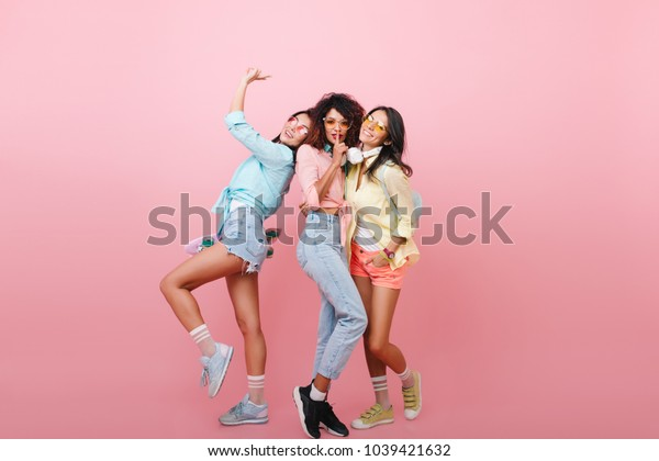 Wonderful brunette asian girl dancing with happy face expression enjoying meeting with friends. Indoor portrait of glamorous three ladies in modern casual clothes. Place for text