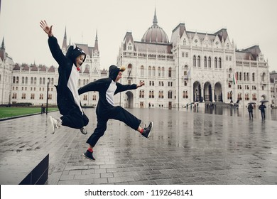 wonderful cheerful couple walking on a rainy Budapest in cat suits