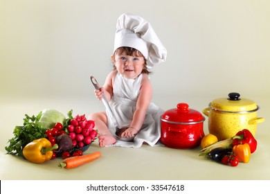 Wonderful child cook in surroundings vegetables and kitchen utensils