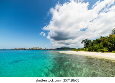 Wonderful colors in the remote Togean Islands, Central Sulawesi, Indonesia. From the white sandy beach to the blue lagoon, with scenic clouds, islets and fishermen village in the background.
