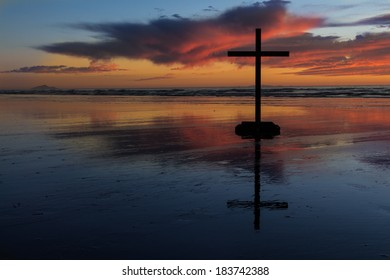 Wonderful colors of sunset behind a black cross.