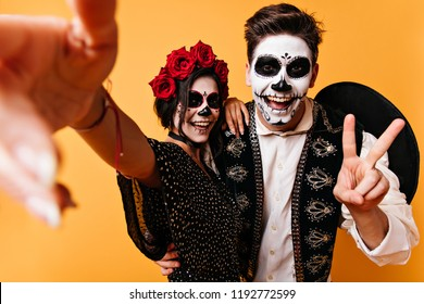 Wonderful couple in halloween costumes making selfie. Smiling lady in mexican attire celebrating day of the dead with boyfriend.