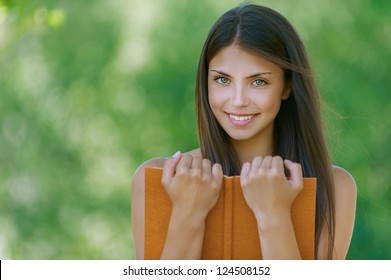 Wonderful dark-haired happy young woman holding an orange book, against background of summer green park.