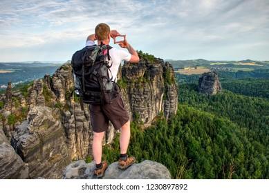 Wonderful daybreak in mountains heavy mist in deep valley. Man on the rock.