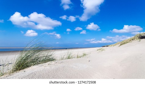 Wonderful dune beach on the North Sea island Langeoog in Germany with sky, clouds, sand and grass on a beautiful summer day