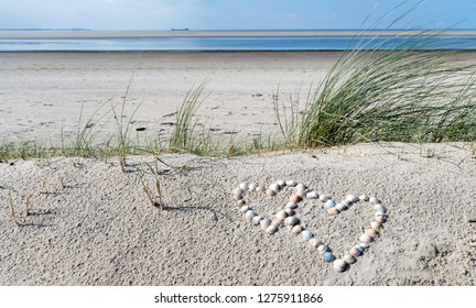 Wonderful dune beach on the North Sea island Langeoog in Germany with sky, clouds, sand, hearts made of sea shells and grass on a beautiful summer day