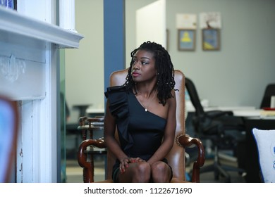 Wonderful elegant African-American woman in black dress sitting in leather armchair looking away