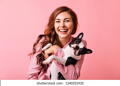 Wonderful european female model chilling in studio with puppy. Indoor portrait of debonair girl enjoying photoshoot with her cute pet.