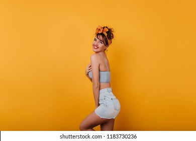 Wonderful european girl with dark hair enjoying leisure time during photoshoot. Studio photo of ecstatic white woman laughing on yellow background and dancing.