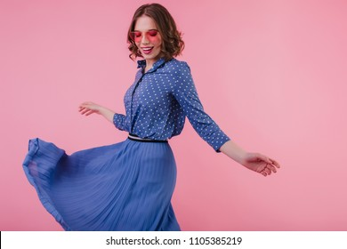 Wonderful european girl with tattoo dancing with inspired smile during studio photoshoot. Indoor portrait of attractive woman in long blue skirt.
