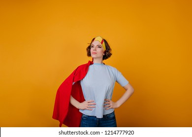 Wonderful female hero in trendy attire posing on yellow background. Pleased curly girl wears crown and red cloak waiting for masquerade.