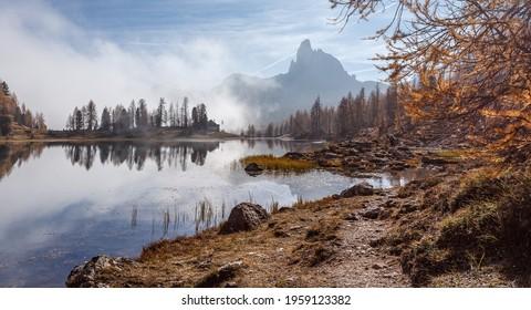 Wonderful foggy autumn landscape. View on Federa Lake early in the morning at autumn during sunrise. Federa lake. Dolomites Alps. Amazing wild nature. Best famouse hiking locations. Great nature scene
