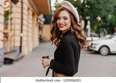 f3aec122 Wonderful ginger woman in beret looking over shoulder. Long-haired smiling  girl drinking coffee