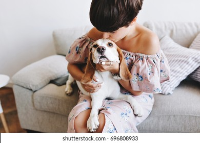 Wonderful girl with trendy short hairstyle kissing beagle dog while sitting on gray sofa. Indoor portrait of amazing young woman in vintage cute dress holding her pet and posing on blur background.