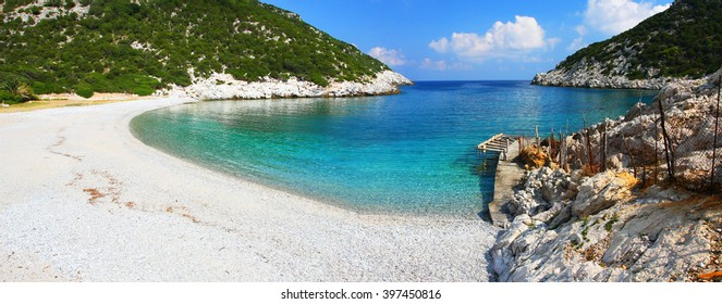 Wonderful Glisteri bay beach with crystal clear water and small wooden port, Skopelos island, Greece