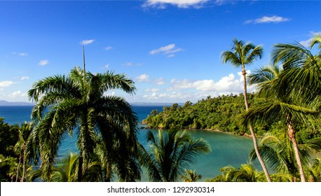 Wonderful holiday on beautiful and lonely sandy beach in a paradise on Samana, Dominican Republic  in the Caribbean with palms, sky, ocean and clouds and beautiful clear water in the ocean