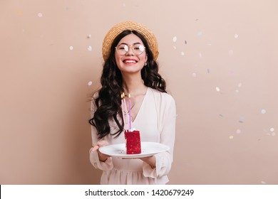 Wonderful japanese girl with curly hair holding cake. Front view of chinese woman in glasses celebrating birthday.