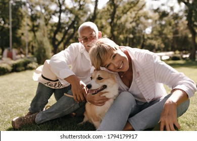Wonderful lady with blonde cool hairstyle in striped blouse and jeans smiling and posing with dog and husband in white shirt in park..