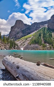 Wonderful lake in the mountains. Big branch in the foreground. The beautiful blue water of Lake Moraine.