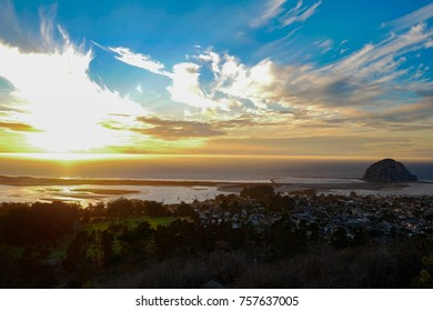 Wonderful landmark of Morro Rock and the sun above the ocean from Black hill trail, Morro Bay California USA.