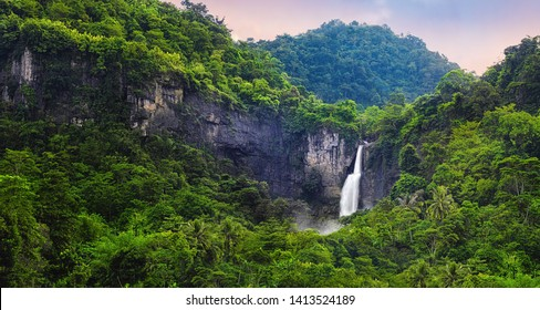 Wonderful Landscape of Cascade Waterfall in Tropical Rainforest. Scenery of Rock Cliff and Cimarinjung Waterfall at UNESCO Global Geopark Ciletuh.